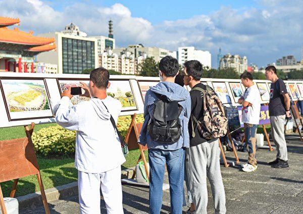 遊客站在真相展版前了解法輪功洪傳世界與被迫害的真相。(明慧網)