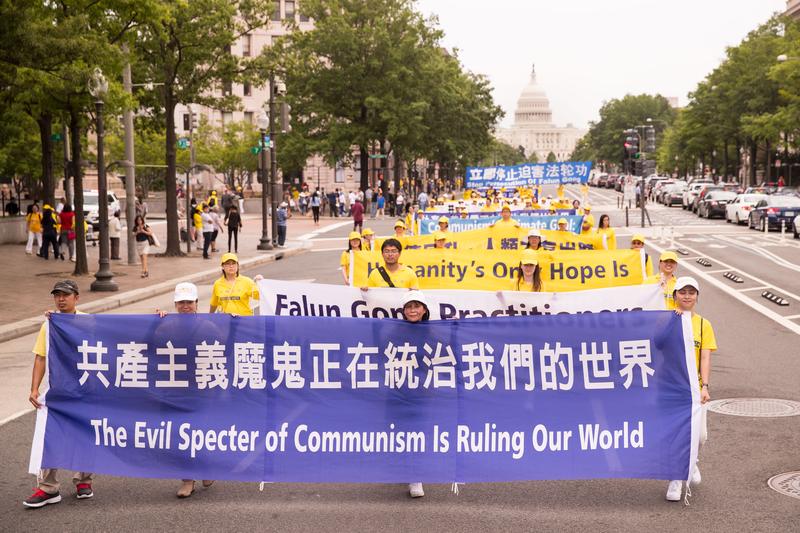 圖為2018年6月20日,全球部份法輪功學員聚集在美國首府華盛頓DC,舉行反迫害集會遊行,法輪功學員以橫幅告訴人們「共產主義魔鬼正在統治我們的世界」。(戴兵/大紀元)