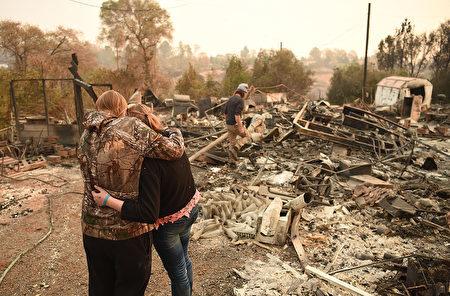 11月18日,一對母女在被加州坎普大火(Camp Fire)焚燬的家園前。當局確認坎普山火造成85人死亡,11人失蹤。(JOSH EDELSON/AFP/Getty Images)