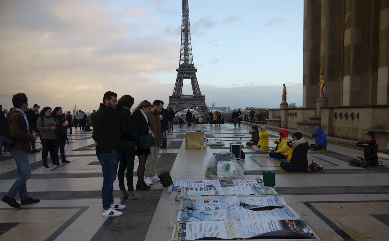 12月9日下午,在巴黎人權廣場,遊人閱讀法輪功真相展板。(明慧網)
