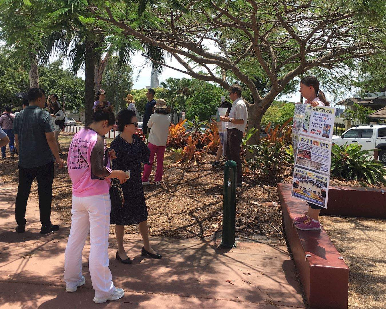 修煉法輪功的西人夫婦John(約翰)和Amanda(阿曼達)向中國遊客展示真相。(明慧網)