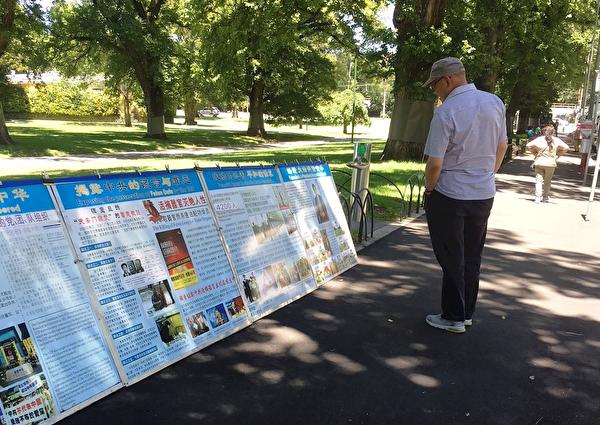 遊客在閱讀真相展板。(明慧網)