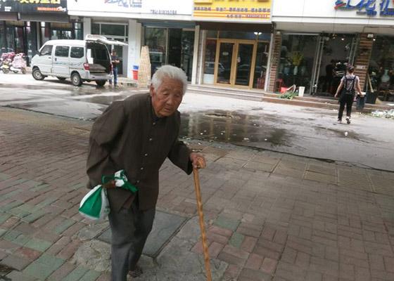 姜淑娥的老母親走在公安局門前的路上。(明慧網)