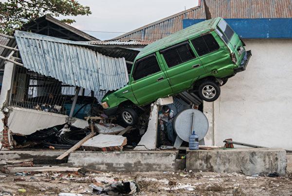 圖為印尼發生強震和海嘯後,一名男子從一輛懸空的汽車下面出來。(Carl Court/Getty Images)
