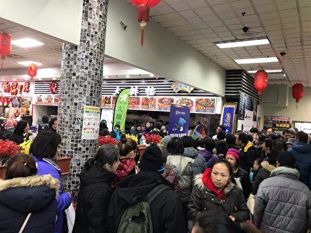 民众在排队领取活动抽奖的各式礼品。