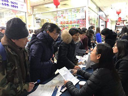 纽约州健保咨询展位的工作人员王小姐在耐心解答民众叶女士(戴眼镜者)其先生为什么没有红蓝卡B部分的问题。