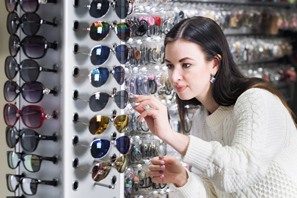 圖為一名女子在商店裏挑選眼鏡。(Fotolia)