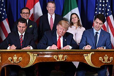 美國總統特朗普(中),加拿大總理杜魯多(Justin Trudeau,右)和墨西哥總統涅托(Enrique Pena Nieto,左)於11月30日在阿根廷G20峰會期間簽署了新的北美自由貿易協定——美墨加協議(USMCA)。後排為三國的貿易談判代表。(SAUL LOEB/AFP/Getty Images)