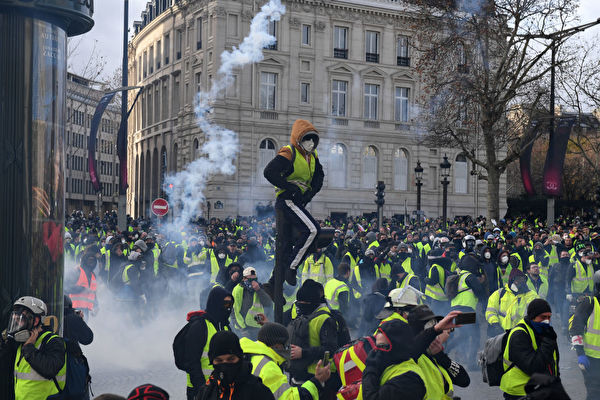 """PARIS, FRANCE - DECEMBER 08: Tear gas is thrown as demonstrators take part in the demonstration of the yellow vests near the Arc de Triomphe on December 08, 2018 in Paris France. ''Yellow Vests' (""""Gilet Jaunes"""" or """"Vestes Jaunes"""") is a protest movement without political affiliation which was inspired by opposition to a new fuel tax. After a month of protests, which have wrecked parts of Paris and other French cities, there are fears the movement has been infiltrated by""""ultra-violent"""" protesters. Today's protest has involved about 5,000 demonstrators so far, who have gathered in the Paris city centre, and police have made at least 211 arrests so far. (Photo by Jeff J Mitchell/Getty Images)"""