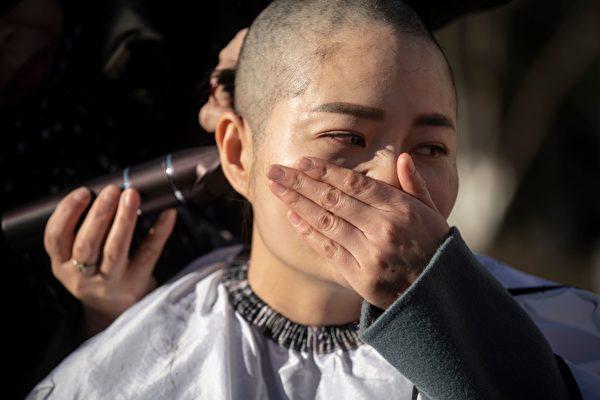 12月17日,709家屬王全璋妻子李文足哭泣著剃光自己的秀髮,以此抗議天津二中院法官違法。(FRED DUFOUR/AFP/Getty Images)