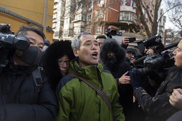 黑龍江維權人士楊春林(綠色外衣)在法院門口高喊聲援王全璋。( NICOLAS ASFOURI/AFP/Getty Images)