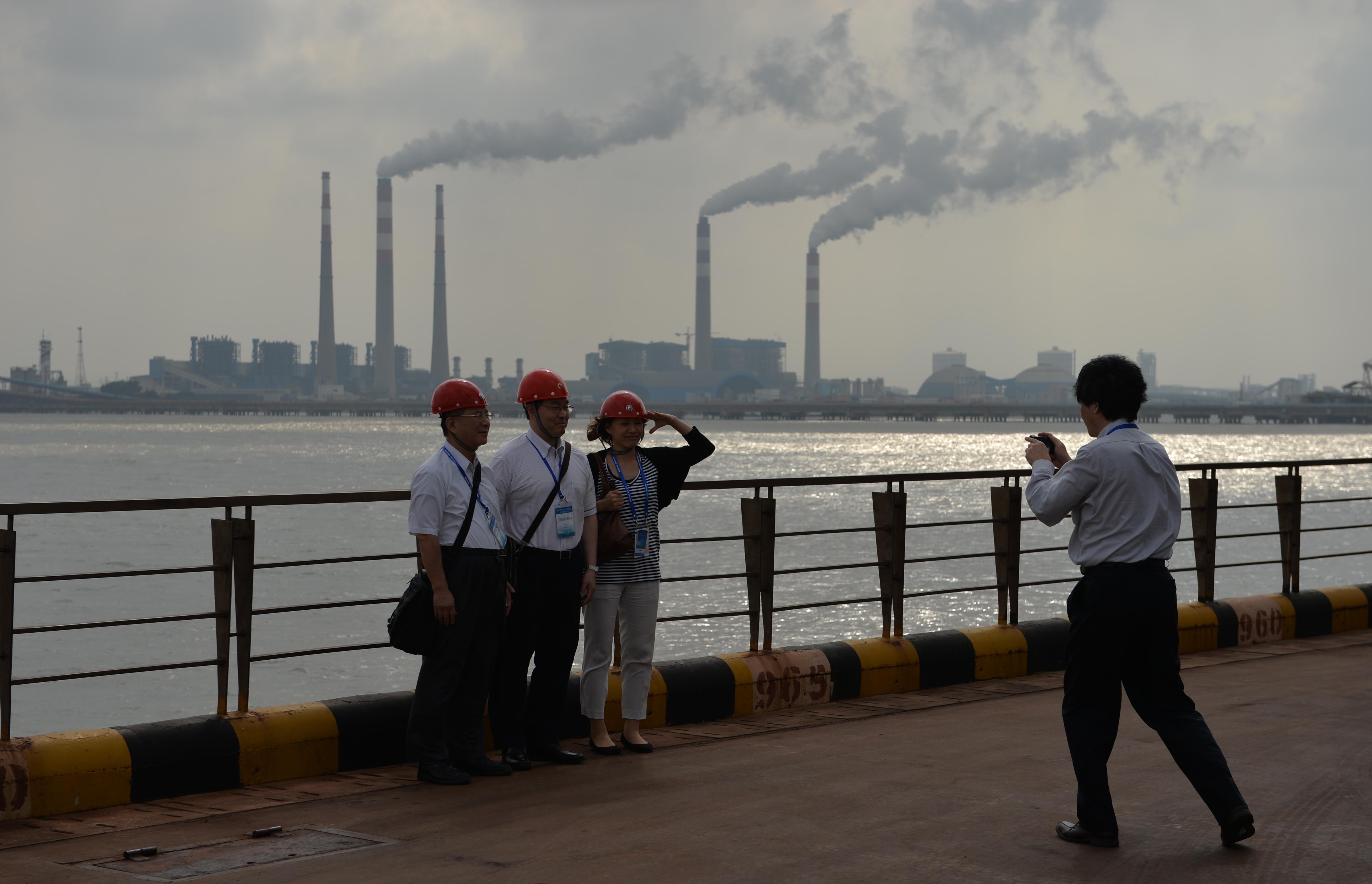 圖為2013年6月6日,幾名參觀者在參觀上海寶鋼鋼廠時拍照,其中一名行左手禮。(PETER PARKS/AFP/Getty Images)
