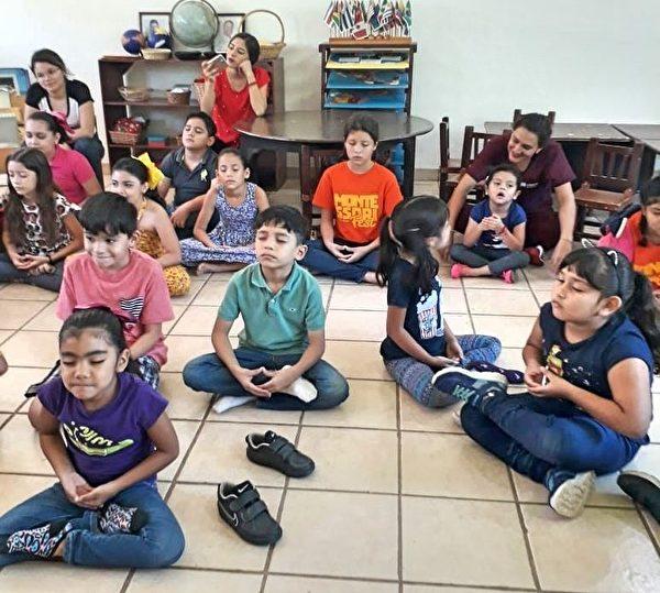 小朋友盤腿坐在地上,學煉來自東方古老修煉的法輪大法。(瓜薩維蒙特梭利學校提供)
