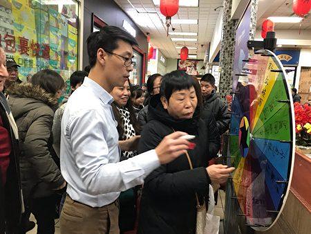 新唐人工作人员(左)与民众做100%中奖活动。