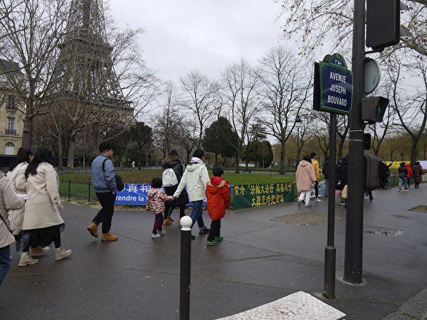 艾菲爾鐵塔下,大陸遊客路經法輪功真相點。(明慧網)