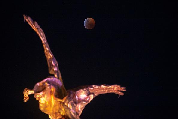 圖為2019年1月21日,三大天文奇觀合一的「超級血狼月」登場,在墨西哥城拍攝到的月全食期間,月亮完全被地球陰影籠罩。(ALFREDO ESTRELLA/AFP/Getty Images)