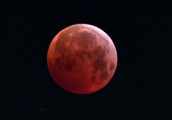 圖為2019年1月21日,三大天文奇觀合一的「超級血狼月」登場,在意大利北部米蘭的月全食期間,月亮完全被地球陰影籠罩。(MIGUEL MEDINA/AFP/Getty Images)
