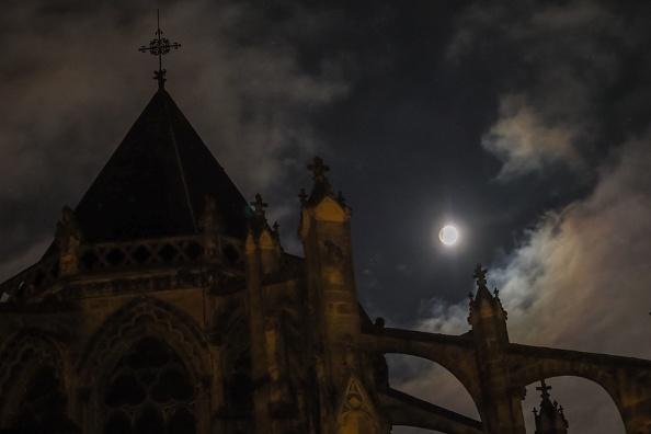 圖為2019年1月21日,三大天文奇觀合一的「超級血狼月」登場,在法國中部的圖爾大教堂後面,月全食期間,月亮開始被地球陰影籠罩。(GUILLAUME SOUVANT/AFP/Getty Images)