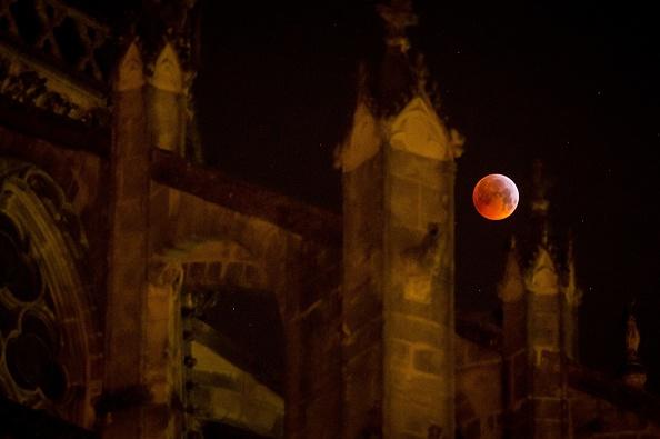 圖為2019年1月21日,三大天文奇觀合一的「超級血狼月」登場,在法國中部的圖爾大教堂後面,月全食期間,月亮完全被地球陰影籠罩。(GUILLAUME SOUVANT/AFP/Getty Images)