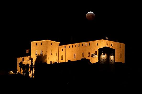 圖為2019年1月21日,三大天文奇觀合一的「超級血狼月」登場,在意大利西北部庫內奧附近的曼塔城堡(Castello della Manta),月全食期間,月亮開始從地球陰影出走。(MARCO BERTORELLO/AFP/Getty Images)