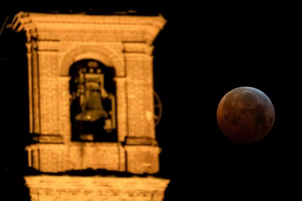 圖為2019年1月21日,三大天文奇觀合一的「超級血狼月」登場,在意大利西北部薩盧佐的「聖貝納迪諾教堂」,月全食期間,月亮完全被地球陰影籠罩。(MARCO BERTORELLO/AFP/Getty Images)