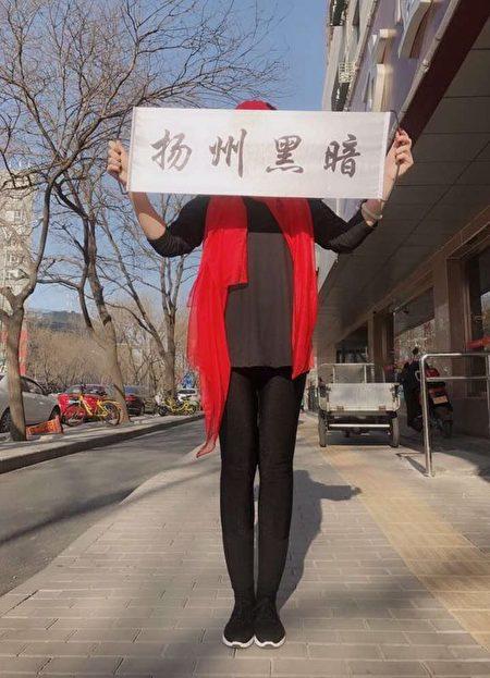 王燕茹在北京舉著「揚州黑暗」的橫幅。(受訪者提供)