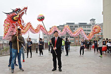 聯大校長蔡東湖與外籍學生體驗火旁龍的樂趣。