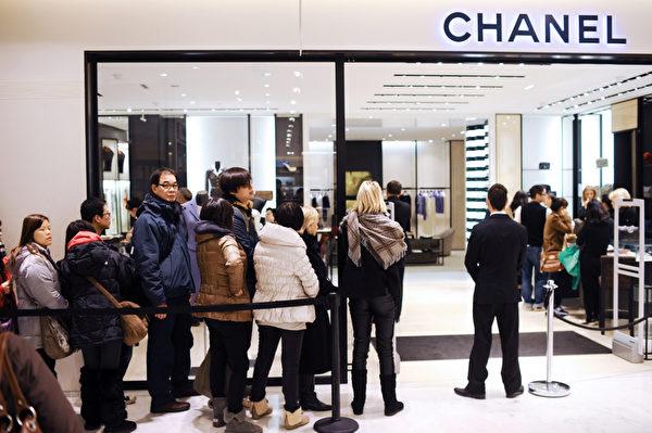 圖為法國巴黎一間百貨公司,民眾排隊準備入內購物。(MARTIN BUREAU/AFP)