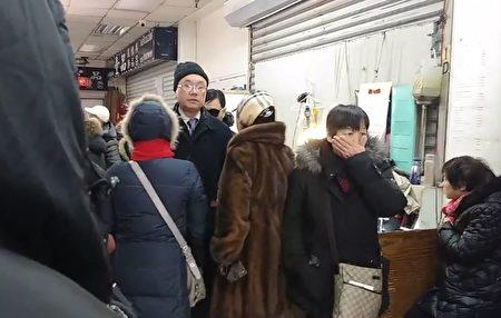 此名在2019年1月13日下午在紐約干擾神韻演出的親共分子(中),2月9日在紅旗佔街結束後,在回收紅旗的店舖內擔任「看場」的角色。(大紀元)