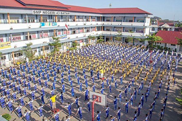 中學生與老師們在大操場上集體學煉法輪功。(明慧網)