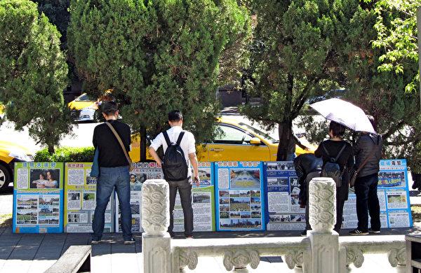 中國遊客在細心閱讀法輪功真相展板。(明慧網)