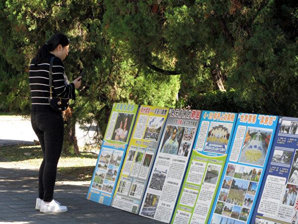 遊客拍攝展板內容,帶回去給親朋好友看。(明慧網)