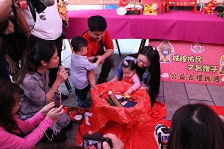 """1岁1个月的萧子芸在父母陪伴下,第一次就抓起代表""""富有、财源广进""""的金元宝。"""