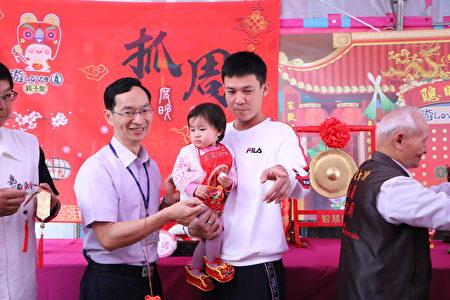 社会处副处长曾建福为小宝贝们亲自戴上城隍爷祈福吊饰。