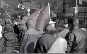 李華紅2月9日上午11點,扛著一面紅旗沿緬街邊走邊指揮紅旗佔街。(大紀元)