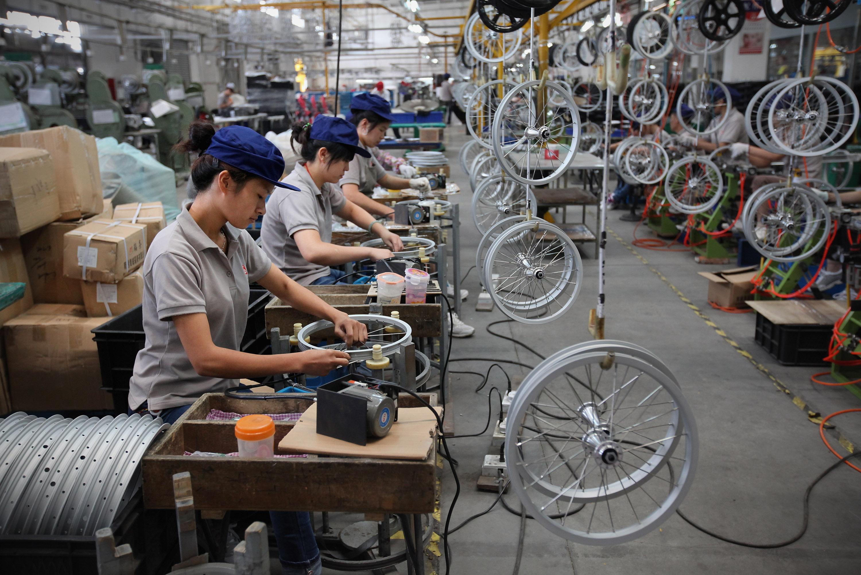 中國江蘇崑山,2012年7月6日,工人們在好孩子集團有限公司的生產線上組裝兒童單車車輪。(Feng li / getty Images)