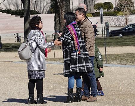 法輪功學員王春榮(左一)在向來自大陸的一家人講述真相。(林樂予/大紀元)