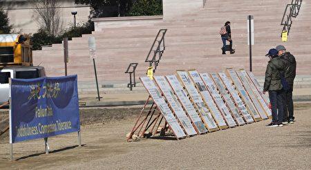中國遊客在法輪功真相展版前駐足閱讀。(林樂予/大紀元)