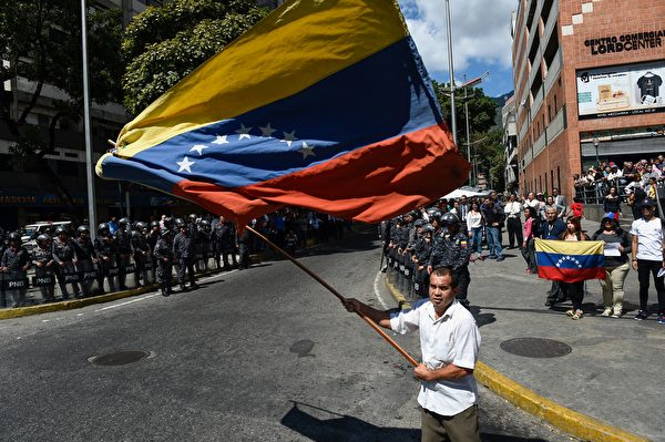 1月30日,瓜伊多在首度加拉加斯再次舉行了抗議活動。圖中為一來自反對派的民眾在揮舞著委內瑞拉國旗。(FEDERICO PARRA/AFP/Getty Images)