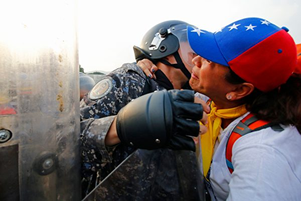 在哥倫比亞邊境Simon Bolivar橋,委內瑞拉人要求國家警察讓提供人道主義援助的物資車輛進入,發生衝突。(SCHNEYDER MENDOZA/AFP/Getty Images)