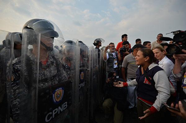 在哥倫比亞邊境Simon Bolivar橋,委內瑞拉人要求國家警察讓提供人道主義援助的物資車輛進入。(LUIS ROBAYO/AFP/Getty Images)