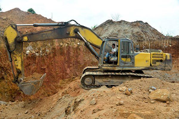 一名中國員工開著重型機械在喀麥隆的一個採礦場施工。(REINNIER KAZE/AFP/Getty Images)
