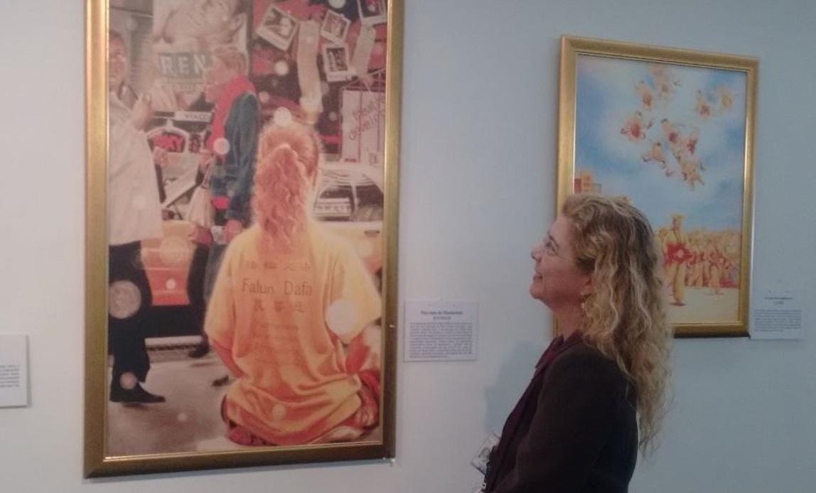 在巴西眾議院工作的埃費林(Evelin)女士站在那幅《曼哈頓街頭》油畫前心情激動。(明慧網)