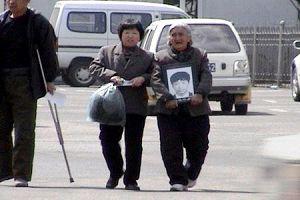 王建國的奶奶抱著孫子的遺像。(明慧網)