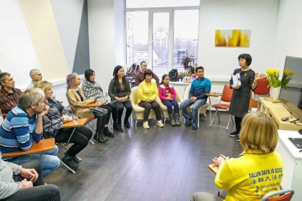 參加者正在聽法輪功學員介紹「法輪功九天學習班」。(明慧網)