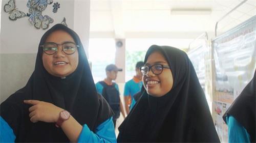 學生Natashah(左)開心地與大家分享了今早學煉法輪功後,肩膀舊患驚喜得到改善的體會。友人Nabila(右)也為她感到開心。(明慧網)