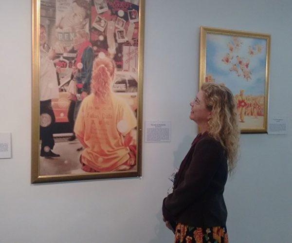 埃費林(Evelin)站在那幅《曼哈頓街頭》油畫前心情激動。(明慧網)