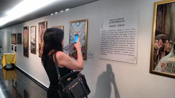住在美國的Sandra觀看畫展,內心受到觸動。(明慧網)