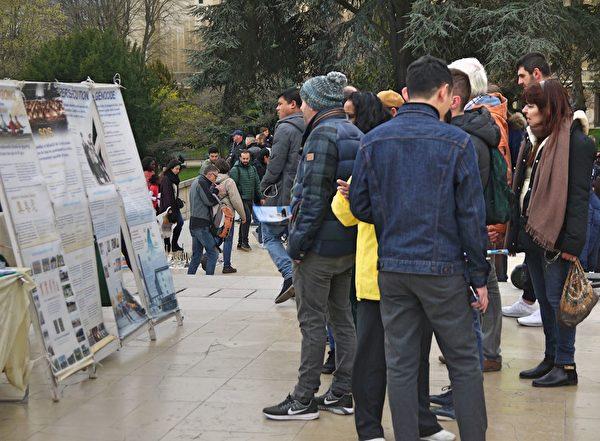許多遊客認真閱讀真相展板,獲取更多的信息。(明慧網)