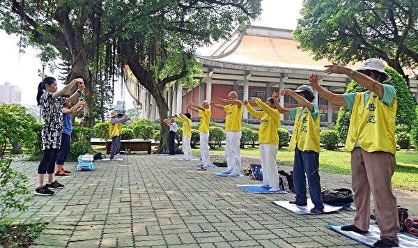 法輪功學員在紀念館景區緊鄰逸仙路的園區樹下煉功。(明慧網)